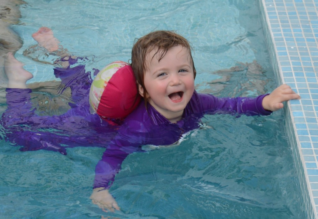 Child swimming in small pool with a floatie attached and smiling