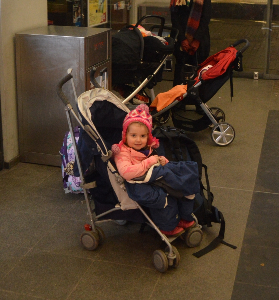 Child sitting in a stroller full of luggage at a train station platform