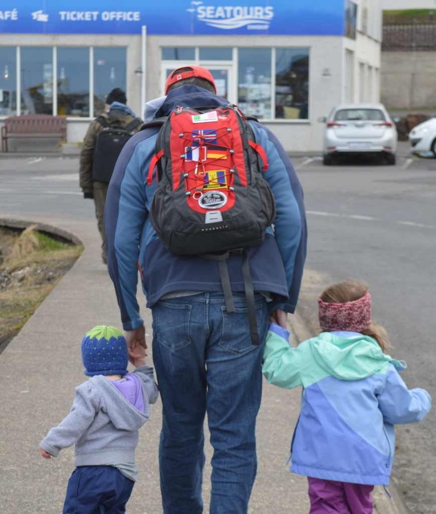 Father walking with two toddlers with a North Face backpack on