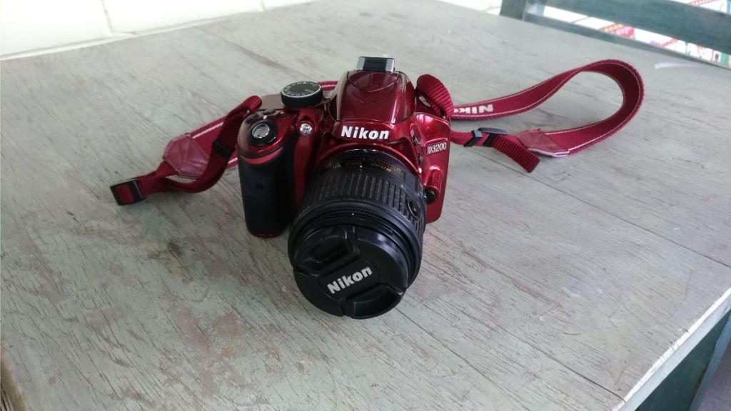 Red Nikon Camera resting on a table