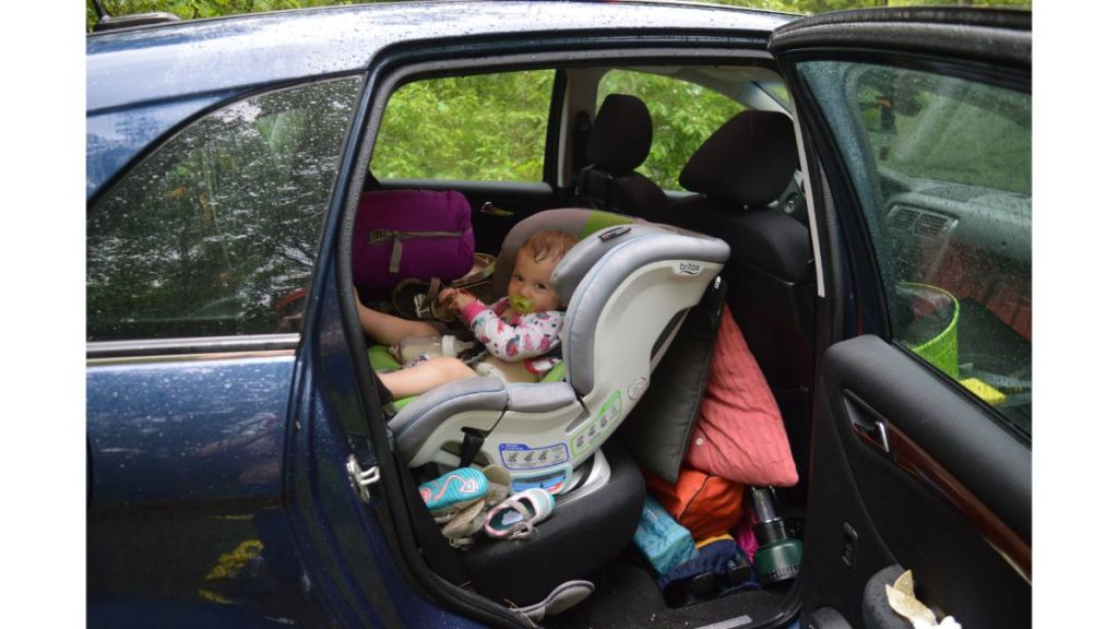 Child in car surrounded with camping gear