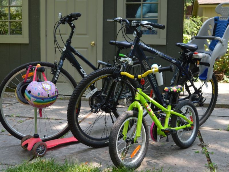 Bikes standing upright with child helmets and carrier seats attached